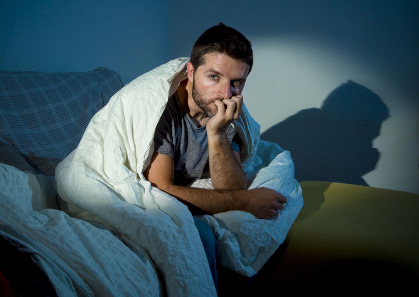 Man sitting on his bed contemplating what his anxiety and depression are trying to tell him.